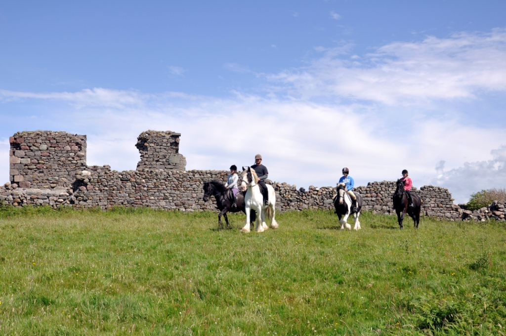 Riders trek alongside the ruins of the Gráinne Uaile Castle on Rose Hill