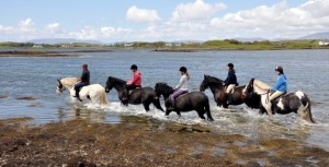 Riders trekking along the shores of Carrowholly